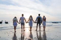 Groupe des jeunes sur la plage aux vacances d'été de coucher du soleil, vue arrière arrière de marche de bord de la mer d'amis Images libres de droits