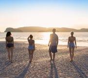 Groupe des jeunes sur la plage aux vacances d'été de coucher du soleil, vue arrière arrière de marche de bord de la mer d'amis Photo libre de droits