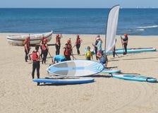 Groupe des jeunes sur la plage dans les costumes pour faire de la planche à voile photo stock