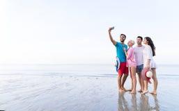 Groupe des jeunes sur la plage prenant la photo de Selfie des vacances d'été futées de téléphone de cellules, vacances de sourire Image stock