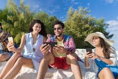 Groupe des jeunes sur la plage utilisant des vacances d'été futées de téléphone de cellules, amis de sourire heureux causant en l Images stock