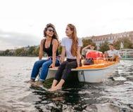 Groupe des jeunes sur un bateau de pédalo Photographie stock libre de droits