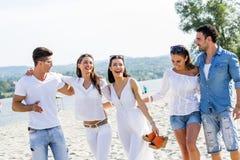 Groupe des jeunes tenant des mains sur la plage Image libre de droits