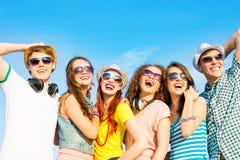 Groupe des lunettes de soleil de port et du chapeau des jeunes Photos stock