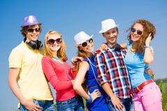 Groupe des lunettes de soleil de port et du chapeau des jeunes Photographie stock libre de droits