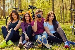 Groupe des personnes détendant après bicyclette montent dans une forêt Photographie stock libre de droits