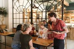 Groupe divers d'amies commandant des boissons d'un serveur de Bistros Photo libre de droits