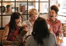 Groupe divers d'amies riant ensemble dans une barre à la mode Image stock