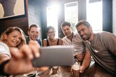 Groupe divers d'amis prenant le selfie au café Image libre de droits