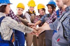 Groupe divers de travailleurs de la construction empilant des mains Images libres de droits