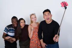 Groupe divers heureux d'amis ethniques multi souriant tout en donnant Image libre de droits