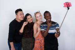 Groupe divers heureux d'amis ethniques multi souriant tout en donnant Photo libre de droits