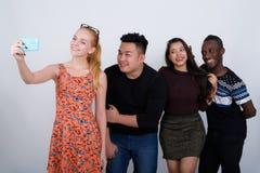 Groupe divers heureux d'amis ethniques multi souriant tout en prenant Image stock