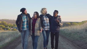 Groupe divers heureux marchant sur le chemin de saleté banque de vidéos