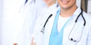 Groupe dos doutores desconhecidos que estão em linha reta no escritório do hospital Feche acima do estetoscópio no peito do médic imagens de stock