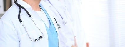 Groupe dos doutores desconhecidos que estão em linha reta no escritório do hospital Feche acima do estetoscópio no peito do médic imagem de stock royalty free