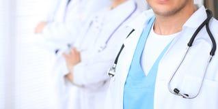 Groupe dos doutores desconhecidos que estão em linha reta no escritório do hospital Feche acima do estetoscópio no peito do médic foto de stock royalty free