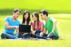 Groupe du jeune étudiant à l'aide de l'ordinateur portatif extérieur Photographie stock