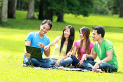 Groupe du jeune étudiant à l'aide de l'ordinateur portatif extérieur Images stock