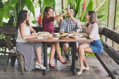 Groupe du meilleur ami quatre ayant l'amusement tandis que déjeuner ensemble au C.A. Images stock
