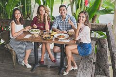 Groupe du meilleur ami quatre prenant le déjeuner leur ensemble à un café Photographie stock