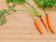 Groupe frais de carottes sur la table en bois Carottes fraîches crues avec la queue Photographie stock