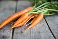 Groupe frais de carottes sur le bois Groupe de carottes fraîches avec l vert Image libre de droits