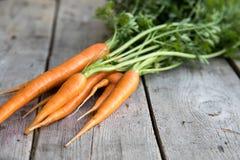 Groupe frais de carottes sur le bois Groupe de carottes fraîches avec l vert Image stock