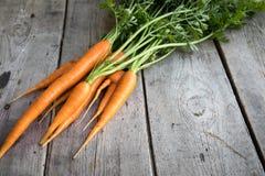 Groupe frais de carottes sur le bois Groupe de carottes fraîches avec l vert Photo stock
