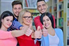 Groupe gai d'étudiants souriant à l'appareil-photo avec des pouces, le succès et apprenant le concept Photographie stock libre de droits