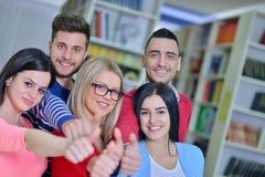 Groupe gai d'étudiants souriant à l'appareil-photo avec des pouces, le succès et apprenant le concept Image stock