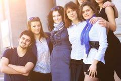 Groupe gai d'étudiants souriant et examinant le cadre Photographie stock libre de droits