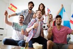 Groupe gai d'amis observant la partie de football à la TV Images libres de droits