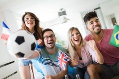 Groupe gai d'amis observant la partie de football à la TV Photos stock
