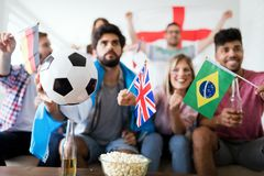Groupe gai d'amis observant la partie de football à la TV Photographie stock