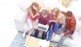 Groupe gai d'amis regardant les clips vidéo sur le lapt Images libres de droits