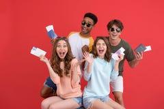Groupe gai d'amis tenant des passeports et des billets images libres de droits