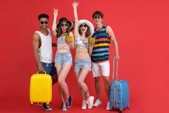 Groupe gai d'amis tenant des valises et des cocktails Images stock