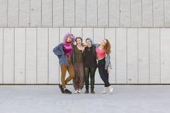 Groupe gai de femmes de l'adolescence étreignant et montrant leur friendshi Photo libre de droits