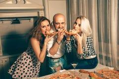 Groupe gai de partie de pizza des jeunes à la maison Image stock