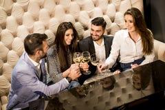 Groupe gai des jeunes grillant avec du vin blanc Image stock