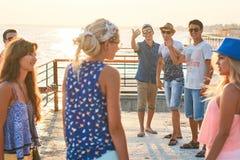 Groupe gai et insouciant d'amis traînant au bord de la mer ensoleillé d'été leurs vacances Photos stock