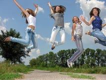 Groupe heureux d'étudiantes sautant dans le village Images stock