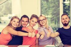 Groupe heureux d'étudiants avec des pouces vers le haut Photographie stock