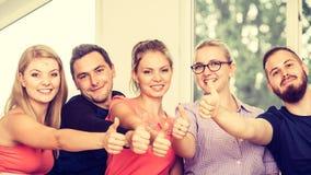 Groupe heureux d'étudiants avec des pouces vers le haut Photo stock