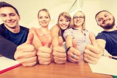 Groupe heureux d'étudiants avec des pouces vers le haut Photos stock