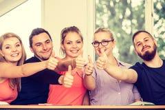 Groupe heureux d'étudiants avec des pouces vers le haut Photographie stock libre de droits