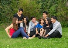 Groupe heureux d'étudiants s'asseyant au parc Image libre de droits