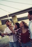 Groupe heureux d'amis allumant des cierges magiques et appréciant la liberté Photos libres de droits