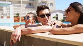Groupe heureux d'amis appréciant la réception au bord de la piscine d'été éclaboussant leurs jambes dans l'eau Jeunes attirants t banque de vidéos